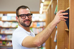 Man picking a book in a library. Young man with glasses picking a book in a library Stock Photography