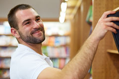 Man picking a book in a library. Young man in polo shirt picking a book in a library Stock Photography