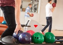 Man Picking Bowling Ball With Friends in Stock Photography
