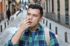 Man picking his nose outdoors.  royalty free stock photo