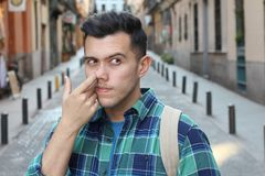 Man picking his nose outdoors royalty free stock photography