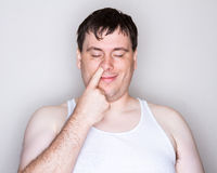 Man picking his nose with a white shirt on. Man looking like he is in heaven picking his nose. Big smile on that face. Just a nice feeling Royalty Free Stock Images
