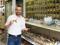 Man picking metal tube extender in household shop Royalty Free Stock Photos