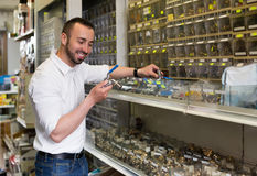 Man picking metal tube extender in household shop Stock Photos