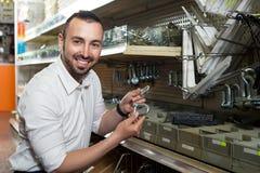 Man picking metallic fastener. Smiling young man picking metallic fastener in household shop royalty free stock images