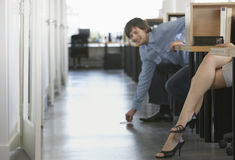 Man Picking Pen Off Floor By Woman's Legs Stock Images