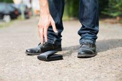 Man picking up fallen wallet Stockbild