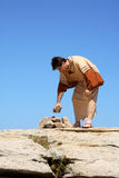 Man picking up rock  - sin Royalty Free Stock Photo