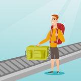 Man picking up suitcase from conveyor belt. Stock Photography