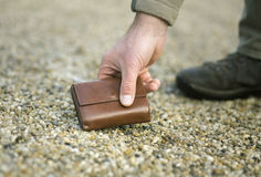 Man picking up wallet Stock Image