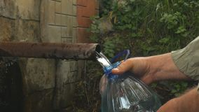 Man hand pours natural spring water into the bottle. stock footage