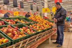 Man picks apples in the supermarket Stock Photos