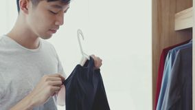 Man picks up a black T-shirt from the wardrobe. stock video footage