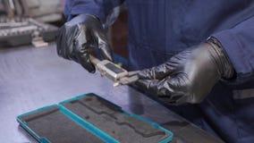 Man picks up an electronic caliper. A man in black gloves picks up an electronic caliper stock footage