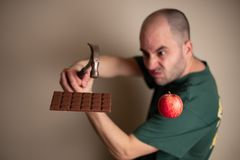 Man picks up a hammer to smash a chocolate bar with one hand and hold an apple with the other stock images