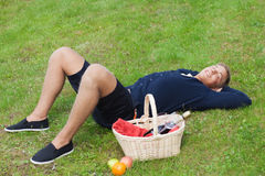 Man on picnic. Young blond guy lying on grass with picnic basket Royalty Free Stock Photo