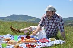 Man on Picnic Eating a Bun Stock Photos