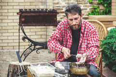 Man on picnic strips pieces of meat on skewer Royalty Free Stock Photo