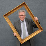 Man with picture frame. Senior  businessman  looking  through empty golden  picture frame in front of face Royalty Free Stock Image