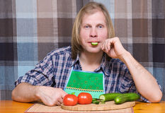 Man with piece of cucumber in the mouth Royalty Free Stock Images