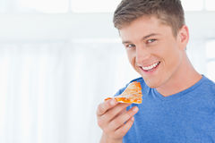 A man with a piece of pizza as he looks at the camera Royalty Free Stock Photos