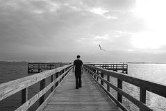 Man on pier. Black and white photo of a Man walking on a pier overlooking the bay royalty free stock images