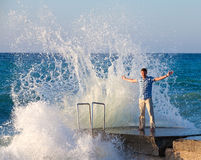 Man on the pier and big wave Royalty Free Stock Image