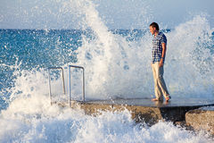Man on the pier and big wave with splashes. Man is staying on the pier in storm Stock Image