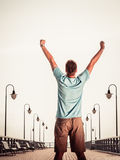 Man on pier with raised hands arms. Freedom. Royalty Free Stock Photography