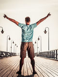 Man on pier with raised hands arms. Freedom. Stock Image