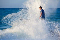 Man on the pier in splashes of the big wave Stock Photo