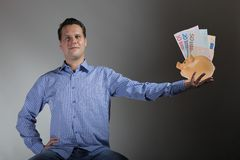 Man with piggy bank and euro banknote Stock Photography