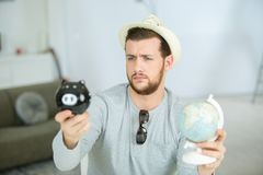 Man with piggy bank and globe. Man with a piggy bank and a globe Royalty Free Stock Image