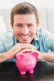 A man with a piggy bank Stock Images