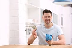 Man with piggy bank and money at home stock photography