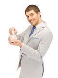 Man with piggy bank and money. Picture of handsome man with piggy bank and money Royalty Free Stock Images
