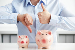 Man with piggy banks showing thumbs up and down. Man with piggy banks showing thumb up and with the second hand thumb down Stock Photo