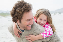 Man piggybacking his daughter at beach Royalty Free Stock Photography