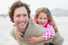 Man piggybacking his daughter at beach Stock Photo