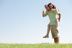 Man Piggybacking His Girlfriend. Happy Young Man Piggybacking His Girlfriend royalty free stock photography