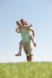Man Piggybacking His Girlfriend. Happy Young Man Piggybacking His Girlfriend stock photography
