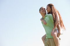 Man Piggybacking His Girlfriend. Happy Young Man Piggybacking His Girlfriend and smile stock photography
