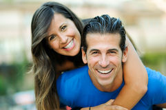 Man piggybacking his pretty girlfriend. Portrait of smiling young men piggybacking his pretty girlfriend in the park Stock Photos