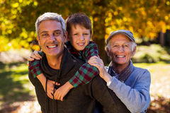 Man piggybacking son while with father at park Stock Images