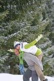 Man piggybacking woman with arms outstretched in snowy woods Royalty Free Stock Photos