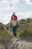 Man Piggybacking Woman On Beach Royalty Free Stock Images