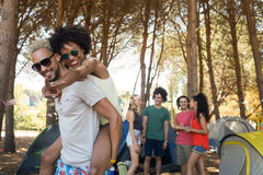 Man piggybacking woman with friends in background Royalty Free Stock Photos
