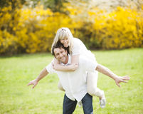Man piggybacking woman in park Royalty Free Stock Photography