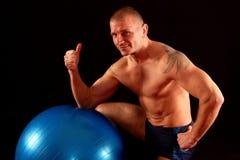 Man with pilates ball shows okay Royalty Free Stock Image