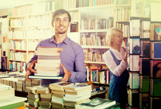 Man with pile of book in book store stock photo